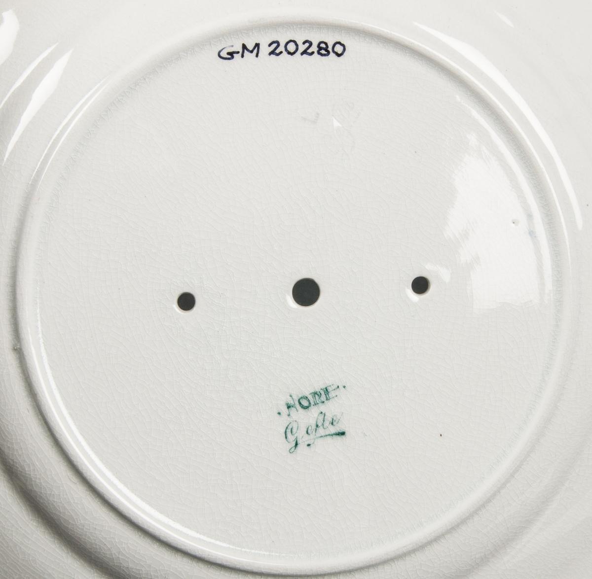 """Tallrik, flat, av flintgods, tillverkad av Gefle Porslinsfabrik, modell -B. Okänd formgivare. Rund med markerat, brett avsatt bräm. Något vågig kant. Rund fotring. Tre hål i spegeln, två fästhål och ett för inkoppling av urverk med visare. Spegeln är dekorerad som en urtavla med siffror och prickar. På bräm koppargravyrtryckt standarddekor """"Nore"""" av gravör Herbert Perje, blågrön broderiliknande kantbård med vita blommor i två- och trepassmönster samt pärlbård mot vit glasyrfond. Blågrön stämpel under """"Nore Gefle""""."""