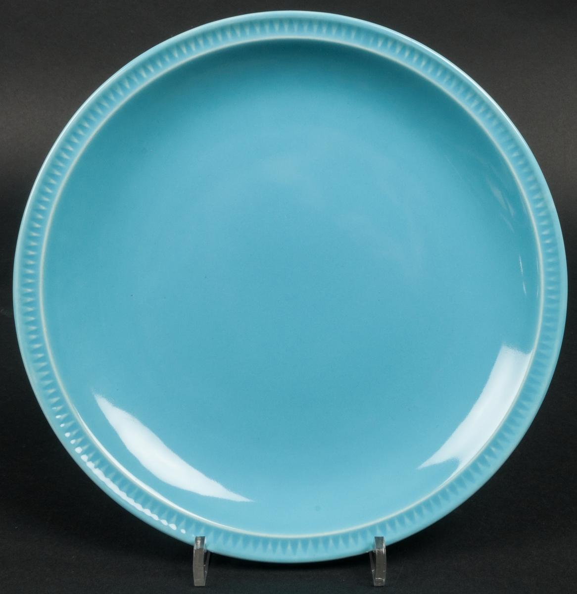 """Tallrik, flat, av flintgods, modell -BE, formgiven av Arthur Percy för Gefle Porslinsfabrik. Rund med taggmönster på minimal bräm. Stor spegel. Stor fotring. Glasyr """"Turkos 2"""", mättad turkos glasyr av Percy 1952. Etikett med blå skorstensstämpel under och skriven text i kulspets """"BE 9"""" fl (Turkos) Indiana No 20""""."""