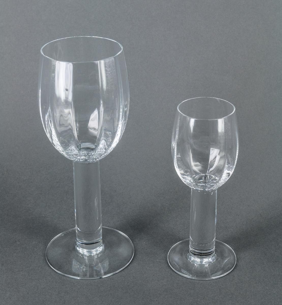 """Sherryglas, ofärgat, modell """"Pelarservisen med optik i kupan"""". Avhugget oval kupa, vertikalt mångkantig på insidan, på högt, cylindriskt, tämligen tjockt ben. Design Gunnar Cyrén för Orrefors Glasbruk."""