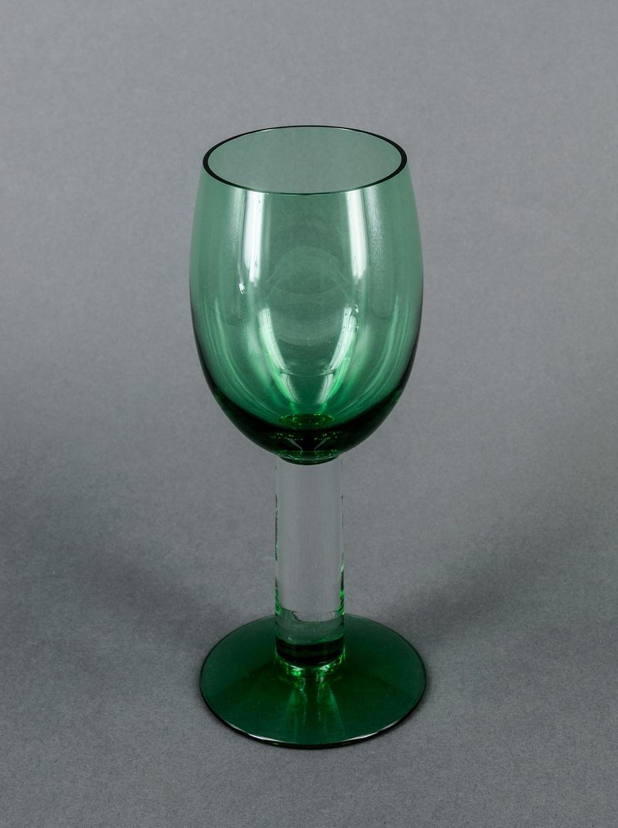 """Vitvinsglas, prov till """"Nobelservisen"""". Avhugget äggformad kupa samt fot i grönt glas. Högt, rakt, runt ben i ofärgat glas. Design Gunnar Cyrén för Orrefors Glasbruk."""