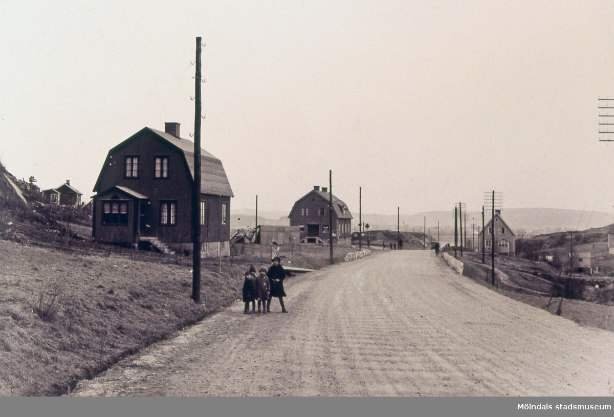Bebyggelse vid Toltorpsgatan i Mölndal. Andra huset på vänster hand är John Gustavssons affär. Huset byggdes 1928 med affär och två lägenheter. Adressen är Toltorpsgatan 65. På gatan står även fyra små barn. Reprofotografi. T 3:23.