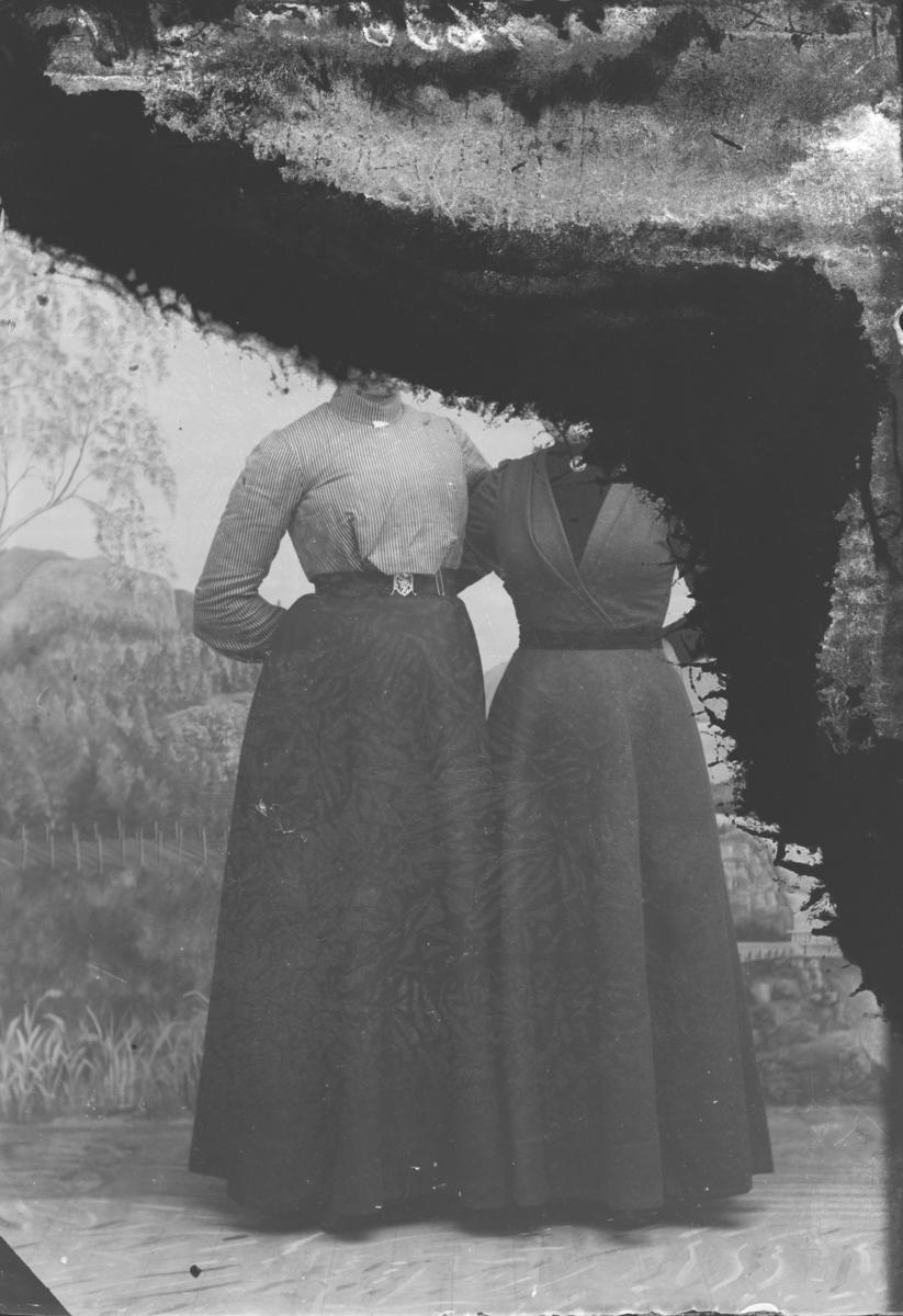 To kvinner som står tett inntil hverandre. Ser ikke hodene da bildet er svart øverst og ned på høyre side. Nevnt Margit H. Rudi.