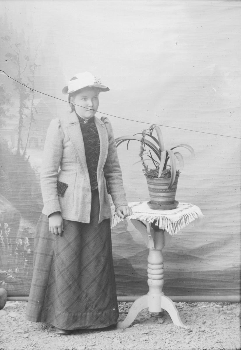 Kvinne står ved bord med blomst. Nevnt som Margit S. Jørstad