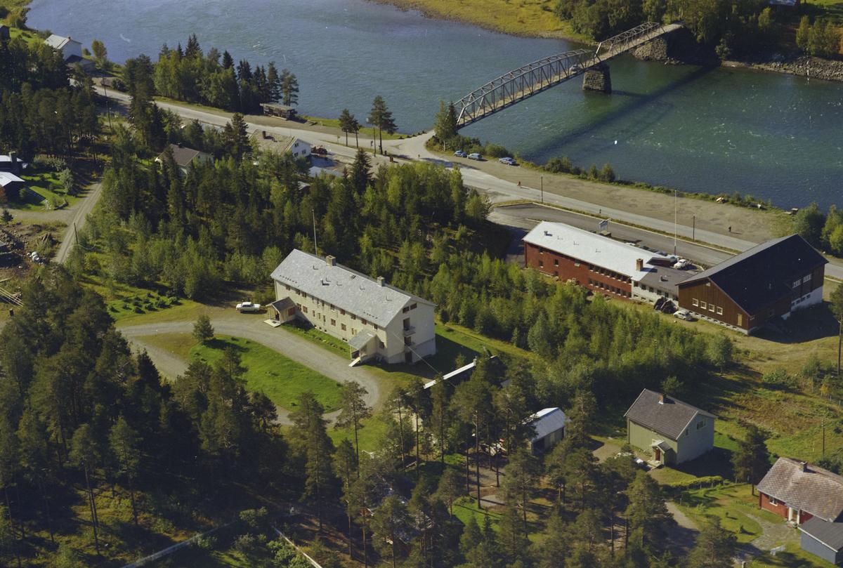 Øyer kommune, Tretten. Lågen med brua, Tretten samfunnshus og Tretten Gamlehjem i forgrunnen, midt på bildet. Gamle E6 mellom bygningene og elva.