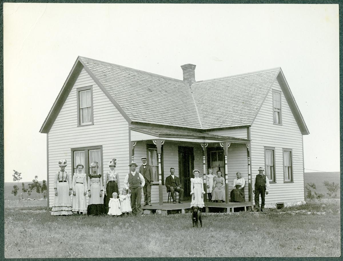 Storfamileien fotografert utenfor våningshuset på en farm i Amerika.