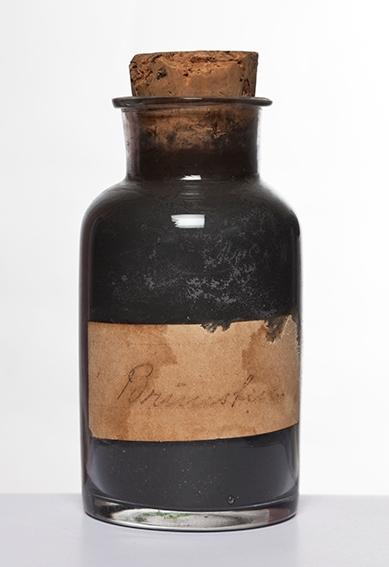 Undervisningsmateriell, Holstad skole, Ås Sylindrisk flaske, kort hals og krage. Innholdet antatt å være pulverisert brunsten.