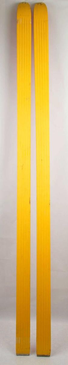 Raude hoppski laga av tre. Gul plastsåle med fem riller. Metallbeslag på baktuppane. Det er bora hol til bindingar. Bruksslitasje.
