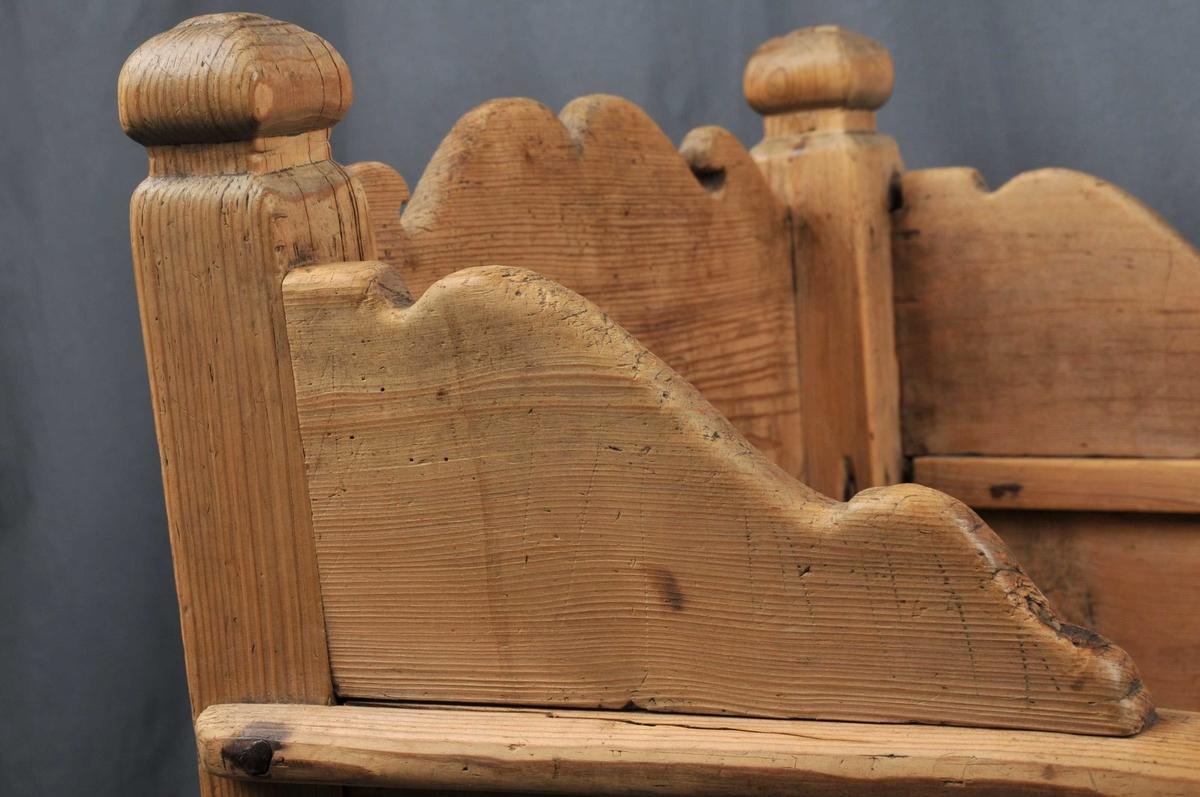 Vogge med nedslitne meiar. Botn er sett saman av 3 bord som ligg lause. Toppen av endeveggane, samt sidekantane er utskorne i bogeformer. Stolpane er firkanta med enkle, utskorne kuler på toppen. Vogga er noko slarkete og slitt.