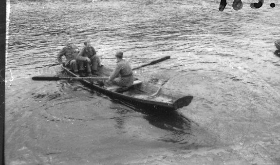 Tre militärer i en roddbåt.