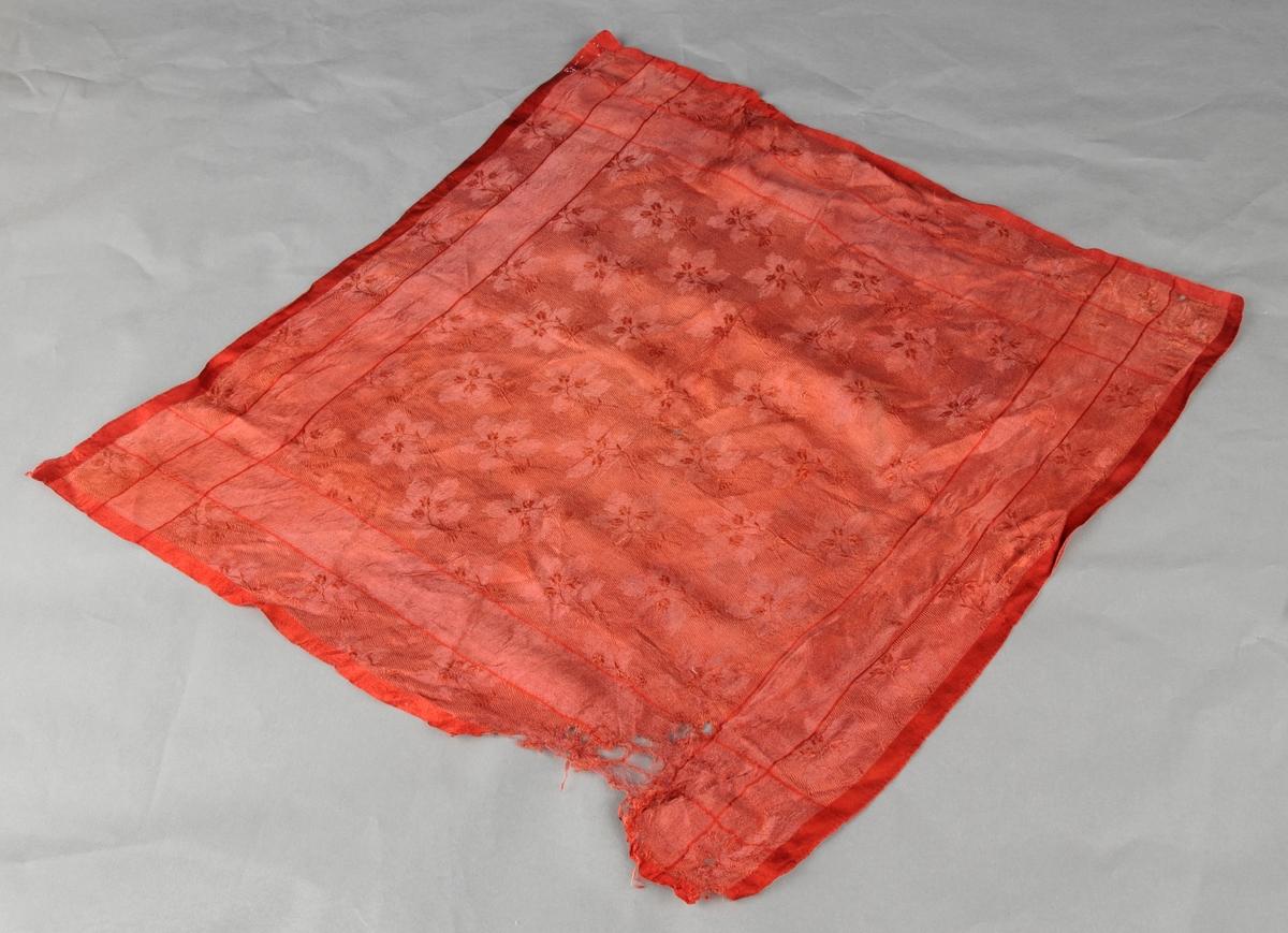 Varmraud silkedamask med vinblad og smale kantar langs sidene. Kvadratisk.