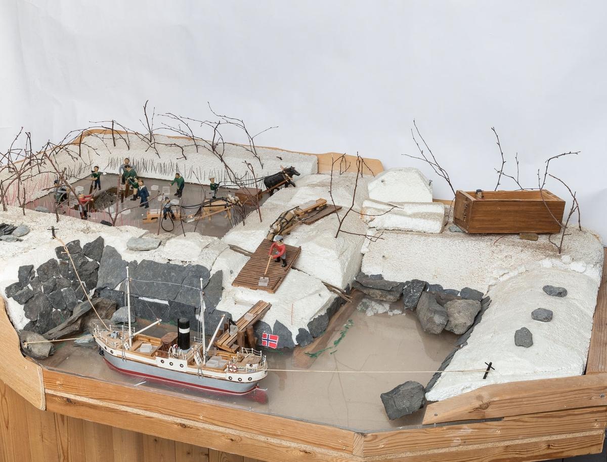 """Modell av isskjæring som kystvirksomhet. Isdam med havn og transportskip. Modellen av """"Anna"""" ved isdammen ble bygget 1990, og er Bækvolds byggenummer 30.  I 1899 ble det fraktet 95000 tonn is til en verdi av 5 mill. kroner. Isdammen i full drift sysselsatte 14 mann og 3 hester."""