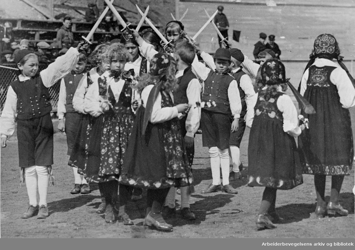 """1. mai 1925, fra barnestevnet på Bislett stadion. Leikarring fra et barnelag som opptrer dansespillet """"Falkvor Lommanson"""" (Sverddansen, Fakkeldansen)."""