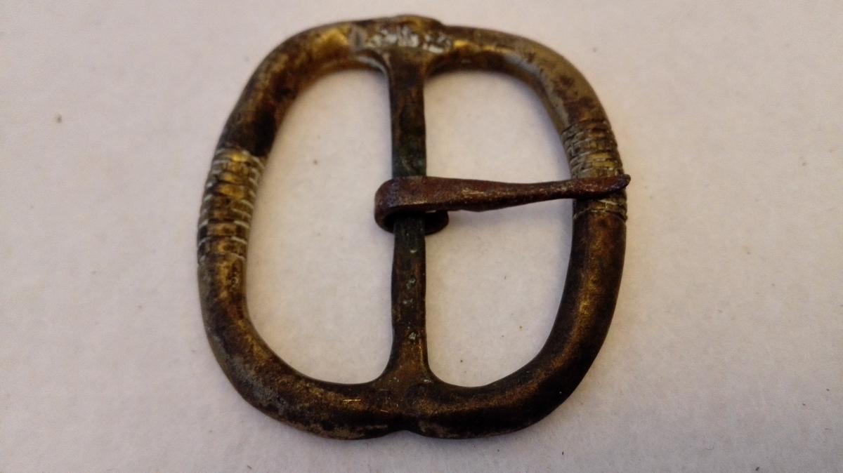 Form: Oval 1 messingspænde.  Stor oval, stöpt messingspænde. Tanden av jern.  Kjöpt av landhandler Theodor Lindström, Lærdal.