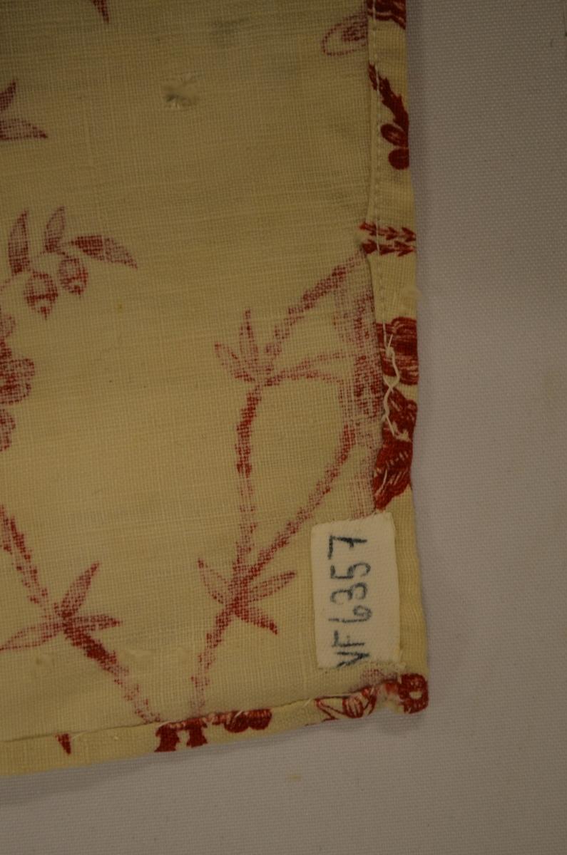 Forkle i ubleika bomullslerret med trykt mønster i raudt. Sett saman av to stykker på lengda. Falda for hand på langsidene. Sekundert falda med maskin i nedrekanten, og i øvre kanten er det tråkla ned ein kant på 6 cm.  Ingen linning.