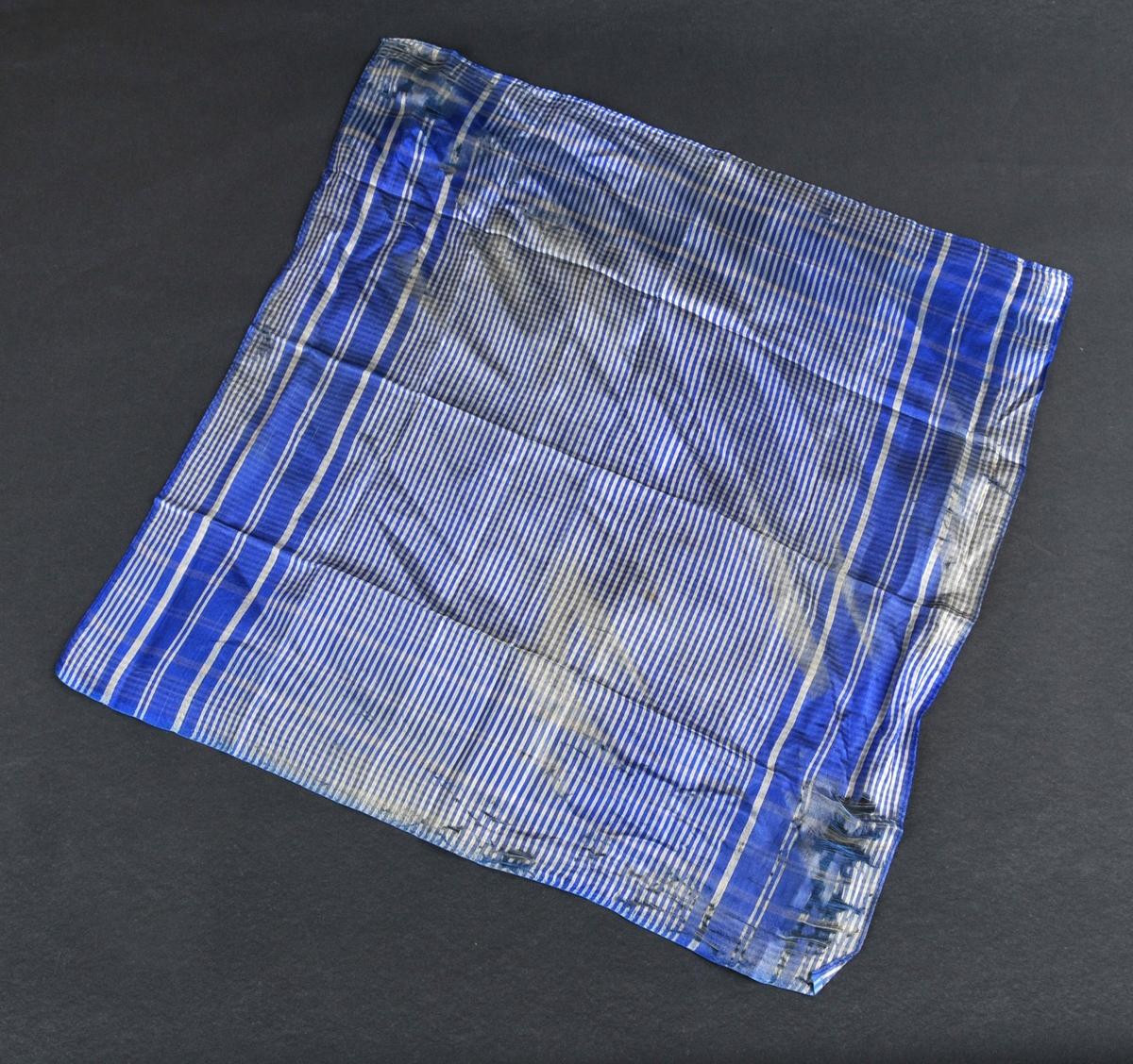 Tynt, lite silketørkle i blått og kvitt stripete mønster. Slitasje i to motståande ender, truleg etter knyting.