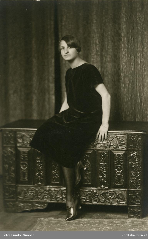 Porträtt av okänd ung kvinna i kort frisyr och mörk klänning sittande på ornamenterad kista. Varuhuset Wertheims porträttateljé, Berlin.