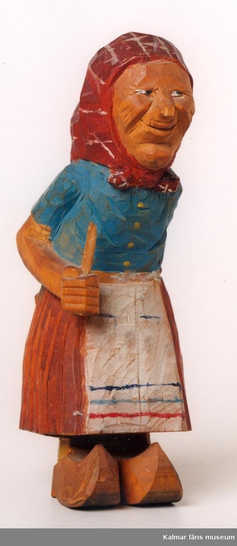 KLM 39255:12. Skulptur, av trä, bemålad i blått, rött och vitt. Gumma med förkläde, blus och sjalett, på fötterna träskor. Defekt, nästippen avslagen. Signatur inristad: G Å. Påskrift i bläck/blyerts:G... Åslago(?).