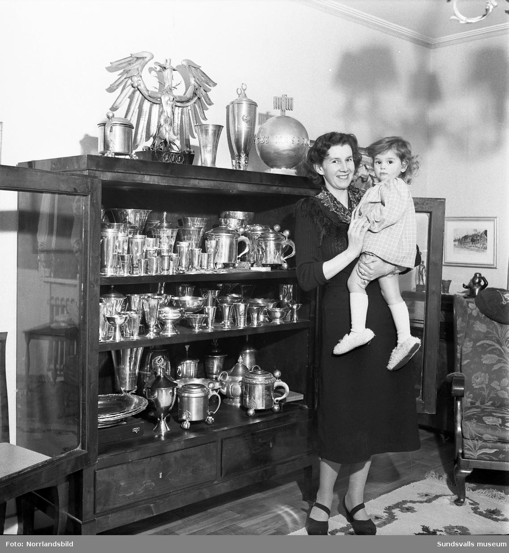 Fru Greta Selånger (Eriksson), samt en dotter, framför sin makes pokalsamling, backhopparen Sven Selånger.