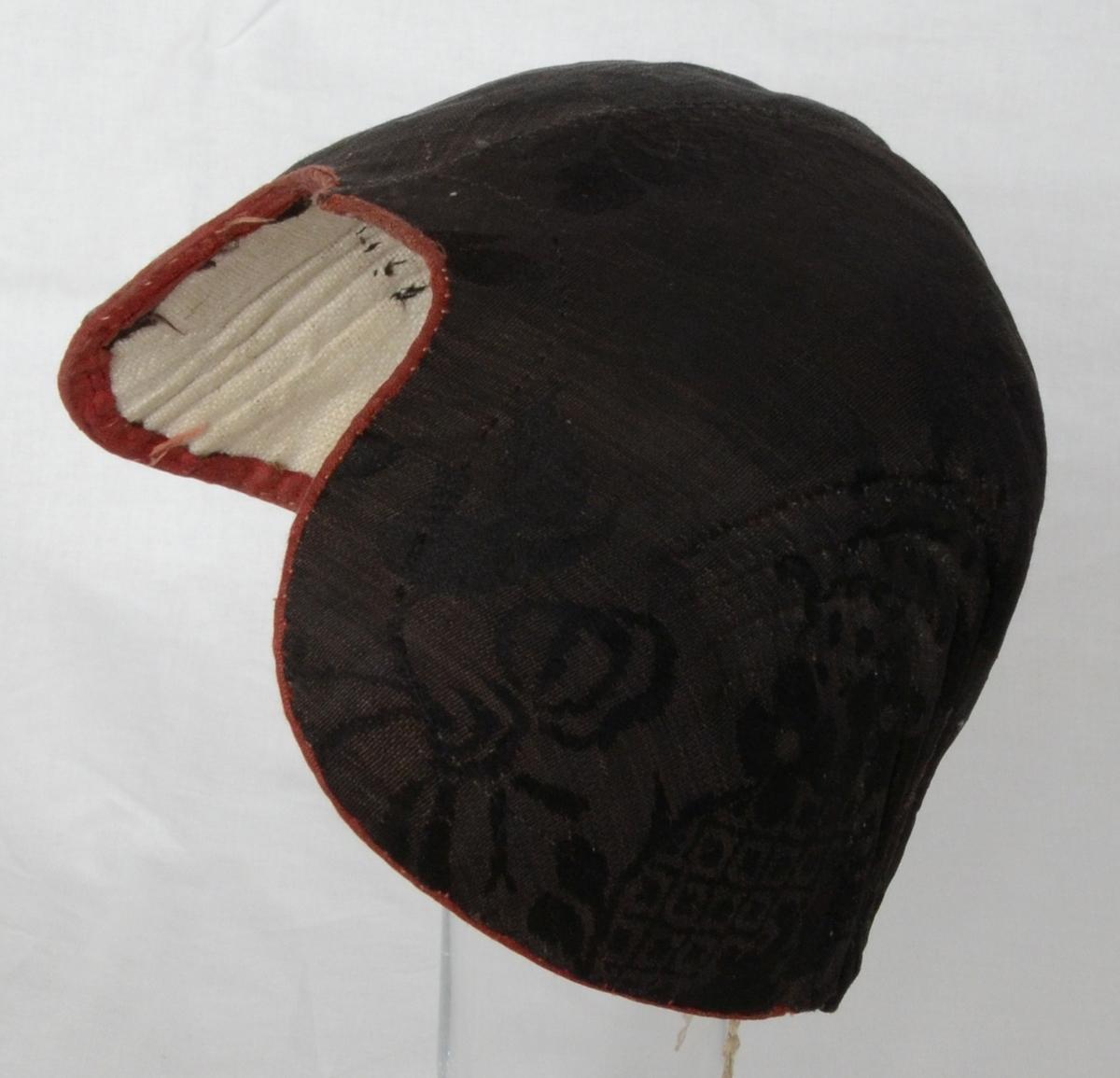 Bindmössa för kvinna av svart, blommigt siden med röd smal kant framtill och hopknutet snöre i nacken.