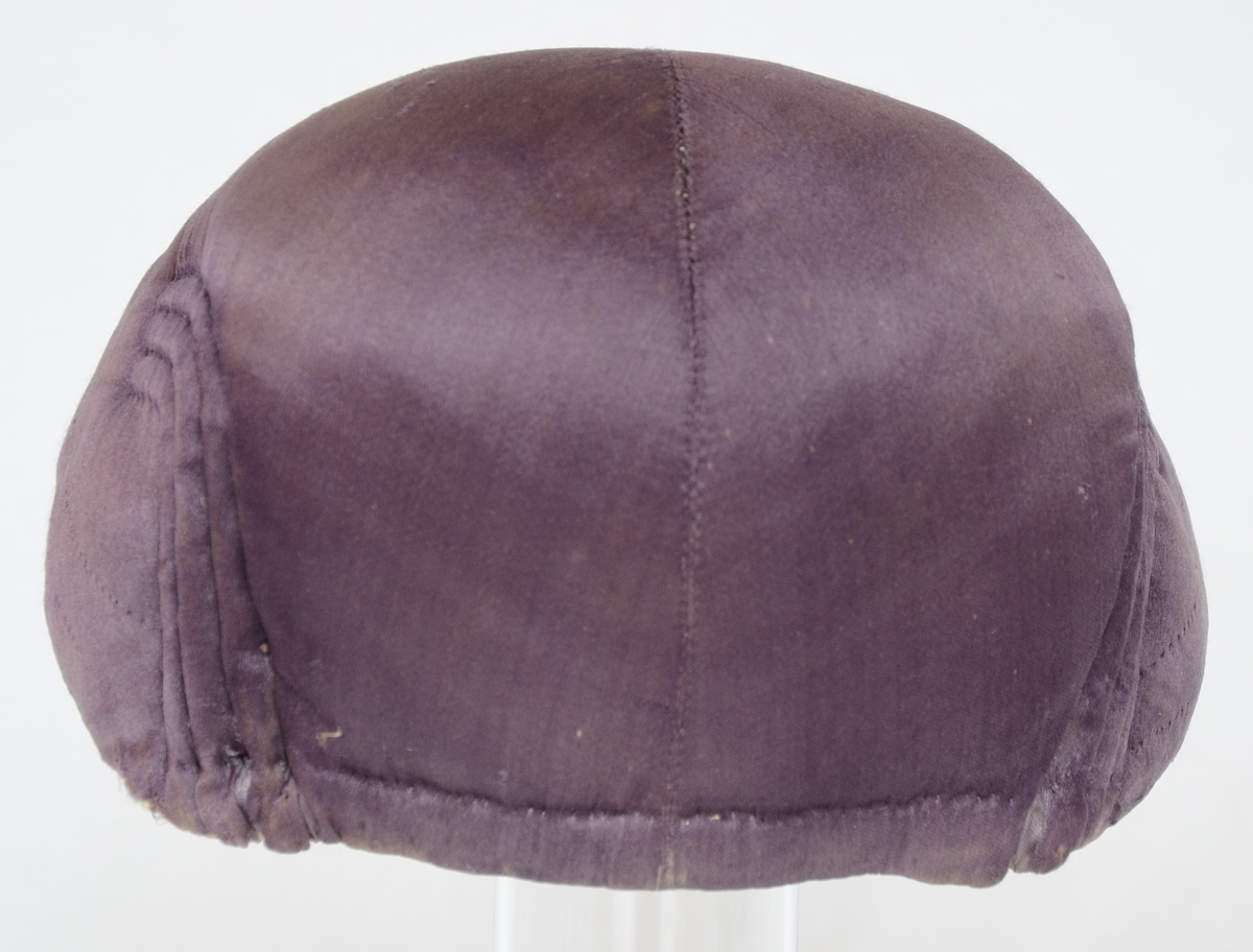 Bindmössa för kvinna av lila siden med söm från nacke till hjässa, fyra skarpa veck på sidorna och hopknutet snöre i nacken.