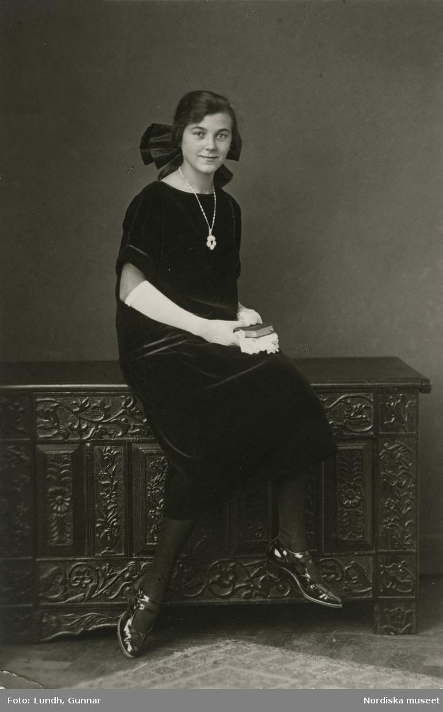 Porträtt av kvinna i mörk klänning, rosett i håret, halsband, vita långa handskar, sittande på en ornamenterad kista. Varuhuset Wertheims porträttateljé, Berlin.