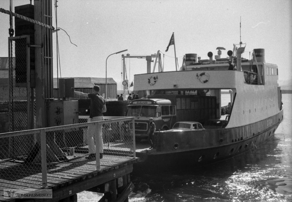 """«Medio juli 1967».Bilfergen """"Eira""""..På ferga står en godsrutevogn Scania-Vabis med karosseri fra Bussbygg, Hovdenakken. Den var registrert T-8585 som tilhørte Måndalen og Innfjorden Billag (MIB). Selskapets logo skimtes over framhjulet. Fargene til MIB var rødt og gult. Bussen var en 1962-modell og gikk i rute Åndalsnes-Molde over Vikebukt hver dag fram til ny buss kom i 1974. Dagen startet med avgang fra Måndalen ca. kl. 8. Så gikk ruten til Vikebukt og den tok ferga til Molde. Den var framme ca. kl. 10. Så var det lossing og lasting i Molde før fergeavgang ca. 13/1330 til Vikebukt. Så var det lossing av varer fra Molde hele veien innover til Åndalsnes, samtidig som det ble lastet inn varer som skulle til Åndalsnes ca. kl. 1630. Der var det igjen lossing og lasting av varer før turen gikk til Måndalen der bilen stod over til neste dag."""