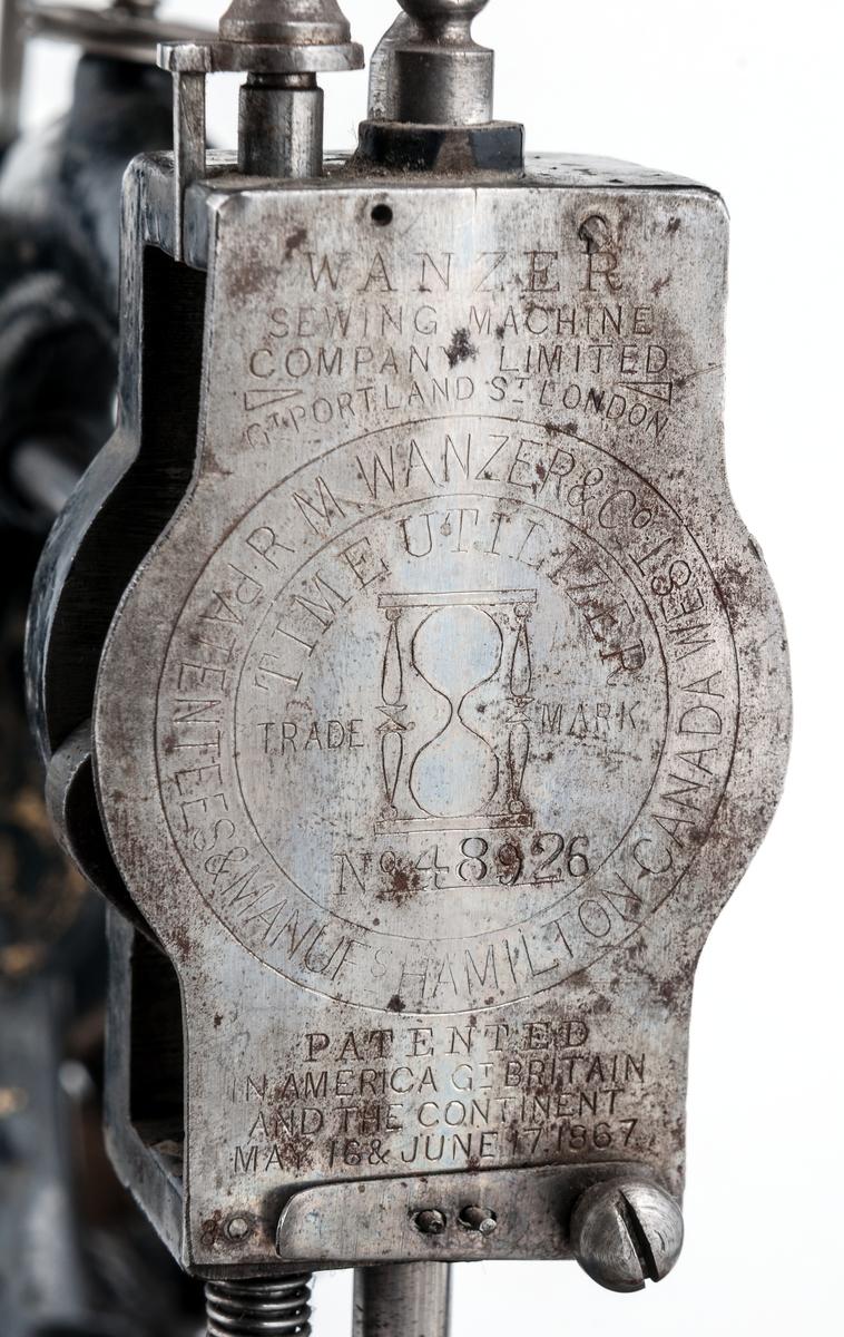 Handsymaskin av järn med handvev vid det lilla svänghjulet. Monterad på vit marmorplatta. Hjuldiameter 16 cm.