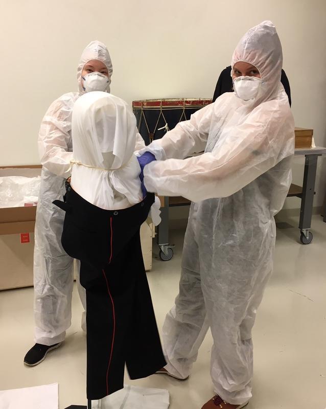 De to finske bachelorstudentene Monna Laari og Saara-Maija Pesonen studerer konservering i Helsinki, og har praksis på konserveringsverkstedet på Ringve Musikkmuseum i vår, der konservator Vera de Bruyn-Ouboter leder arbeidet. Her skal de kle dukker i to gamle og slitte korpsuniformer. De to studentene bruker vernedrakt og masker fordi uniformene tidligere har blitt behandlet med insektmiddel, et giftig stoff som ikke lenger er i bruk.