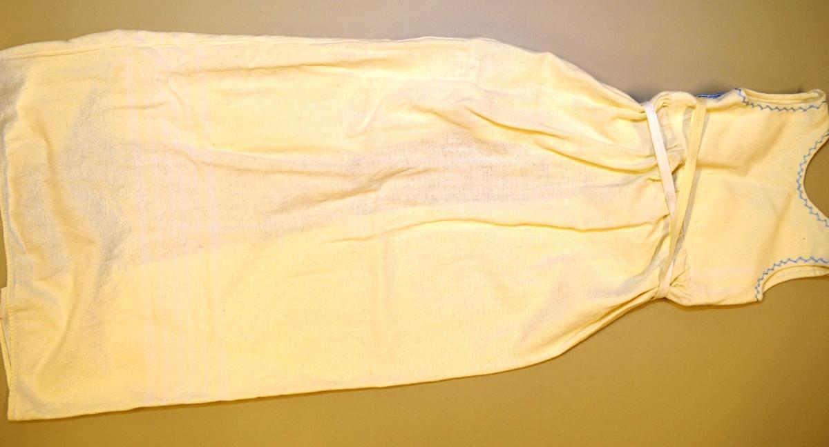 """Løyert, maskinsydd i kvit bomullflanell. To knyteband bak. Knapp og knappehol på båe skuldtene. Broderte kryssesting i blått moulinegarn rundt ermlinning og hals. Overdelen er fóra, """"Skjørtet"""" såvidt rynka."""