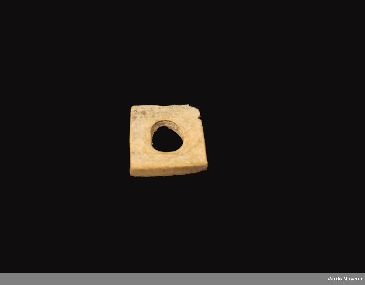 Firkantet og porøs, hull i midten på ca. 2,3  cm i diamanter.