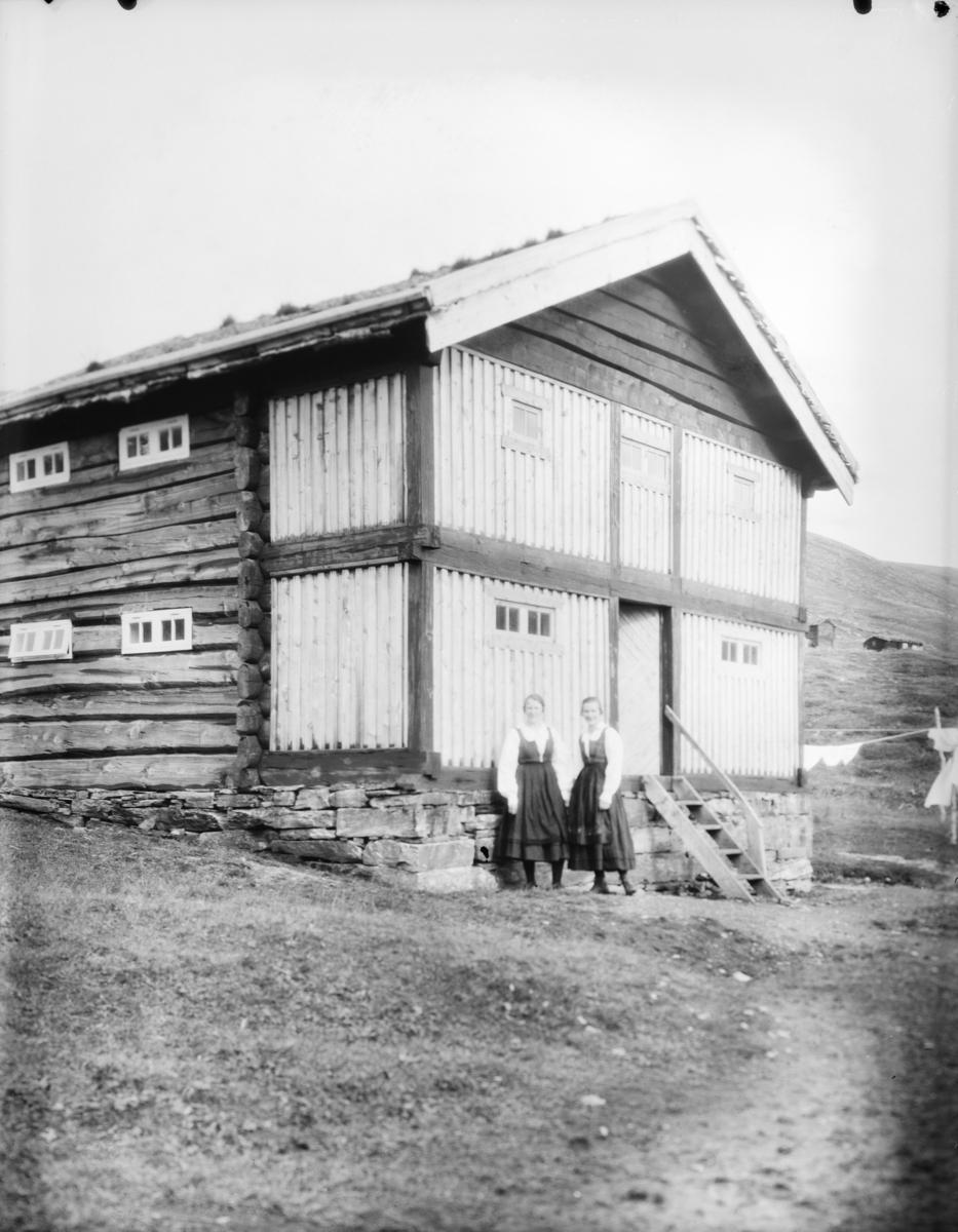 Sjodalen, to kvinner i bunad ved et stabbur eller loft ved Bessheim