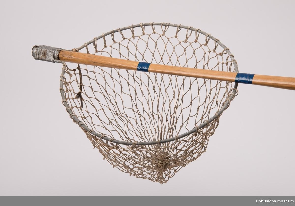 Hopsatt längd 103 cm. Löstagbart skaft som hålls fast med en pinne av koppar i läderband. Ring av galvaniserat järn. Nät av bomull. Skaft av trä förstärkt med blå plasttejp på tre ställen.¨  Samtidiga förvärv även UM024634, UM024635, UM024196, UM024232 - UM024248. Det löstagbara skaftet saknades vid inventering 1996-07-24.  Intervju med Stig Börjesson förvaras under Intervjuserien, Etnologi, Ämbetsarkivet. Föremål för camping, sportfiske och skidåkning från samma givare, se: UM023741-UM023750, UM024196, UM024232-UM024248, UM024251, UM024634, UM024635, UM024790, UM025065 - UM025074.