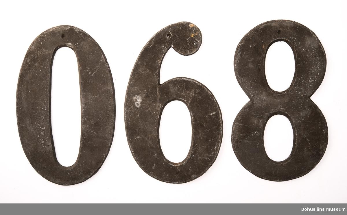 3 psalmnummersiffror av bly, , höjd 13 cm.  0, 6, 8. UM005660:029-031.  Ur handskrivna katalogen 1957-1958: Trälåda m. siffror för psalmnummer 1-8: Bly. H.: 16 cm, m. utsirningar 9-19: Bly. H.: 9 à 10 cm; m. utsirningar. 20-28: Bly o mässing. H.: 15 cm. 29-31 Bly H.: 13 cm. 32-42: Bly o mässing. H.: 10 cm. 43-51: Bly o mässing. H.: 7 cm. 52-54: Gjutna av gulmetall. H.: 10 cm. 55-56: Vitmålad järnplåt. 57: Bly. H.: 10,5 cm.  Lappkatalog: 13