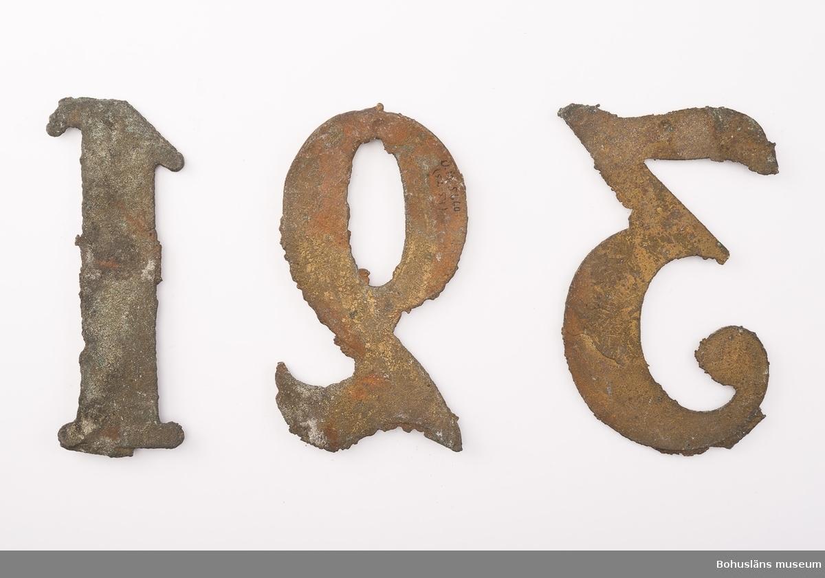3 psalmnummersiffror gjutna av gulmetall, höjd 10 cm.  1, 2, 3. UM005660:052-054.  Ur handskrivna katalogen 1957-1958: Trälåda m. siffror för psalmnummer 1-8: Bly. H.: 16 cm, m. utsirningar 9-19: Bly. H.: 9 à 10 cm; m. utsirningar. 20-28: Bly o mässing. H.: 15 cm. 29-31 Bly H.: 13 cm. 32-42: Bly o mässing. H.: 10 cm. 43-51: Bly o mässing. H.: 7 cm. 52-54: Gjutna av gulmetall. H.: 10 cm. 55-56: Vitmålad järnplåt. 57: Bly. H.: 10,5 cm.  Lappkatalog: 13