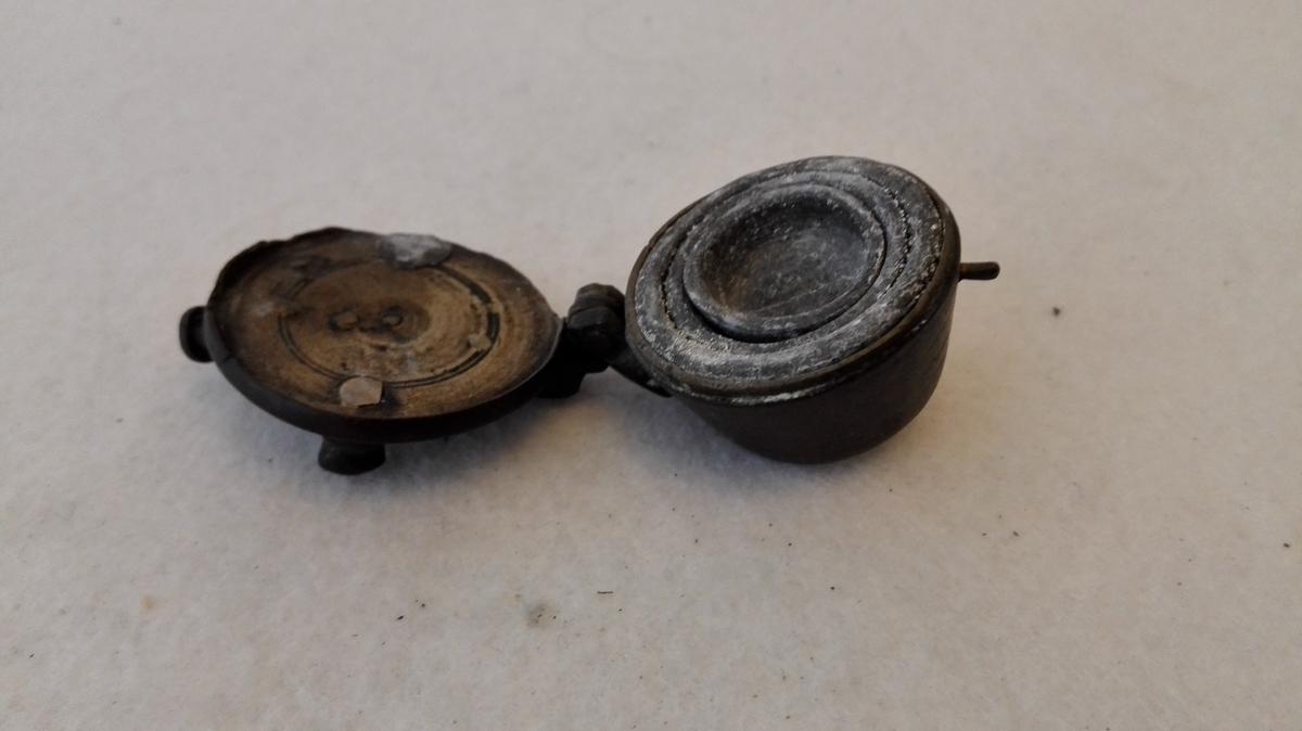 3 skaalformete vegtlodder i messingskaal.  Vegtlodder som no 200 men mindre. Dreiet messingskaal med laag i hængsler, hvori 3 skaalformete lodder, der staar i hinanden.  Lodderne er av bly og under bunden mærket 2 - 1 - 1/2, formentlig lodd der mangler, muligens et.  Gave fra gaardbruker Frik Kvamme, Indre Kvamsö.