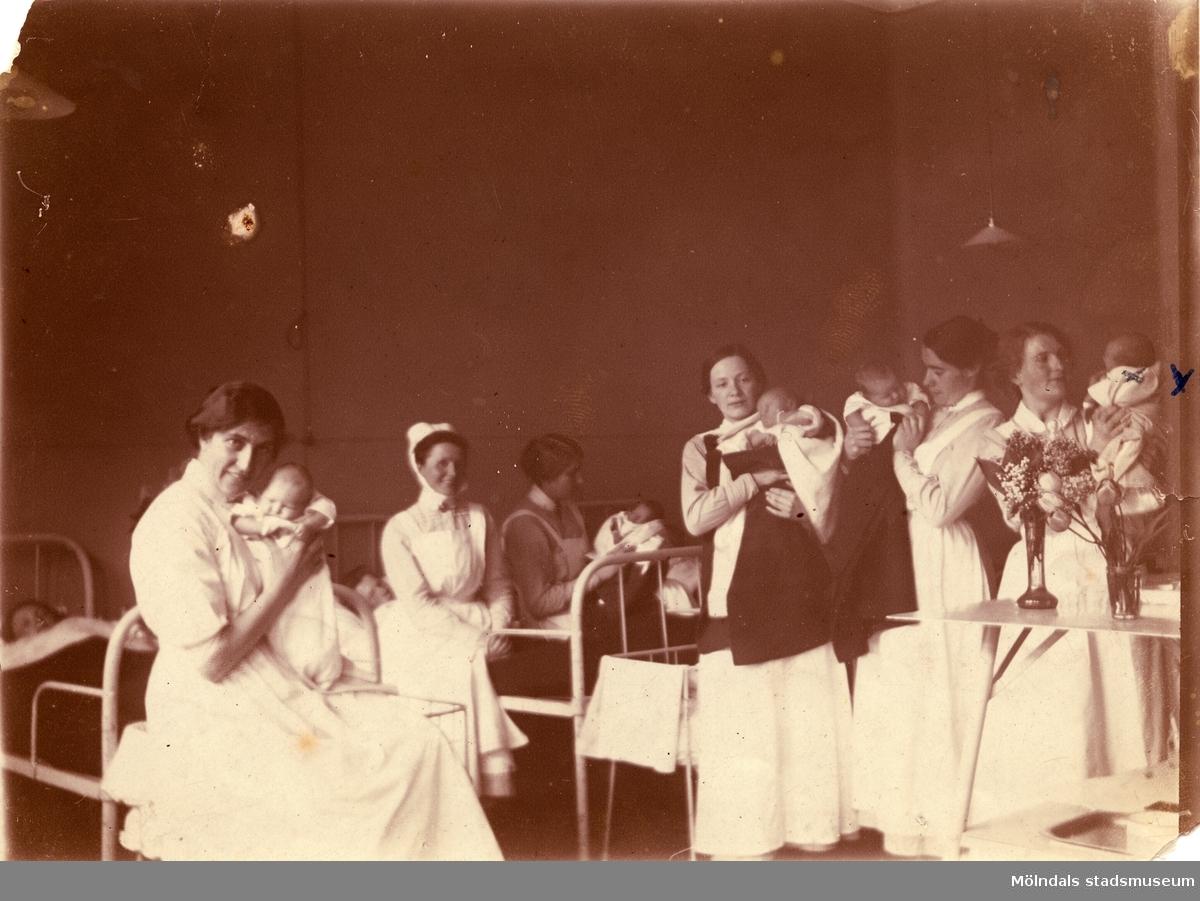 Fotografi från BB på Sprängkullsgatan i Göteborg, år 1916. Nyfödda Elna Börjesson (gift Kristoffersson) syns längst till höger. Modern Hilda Börjesson är skymd.