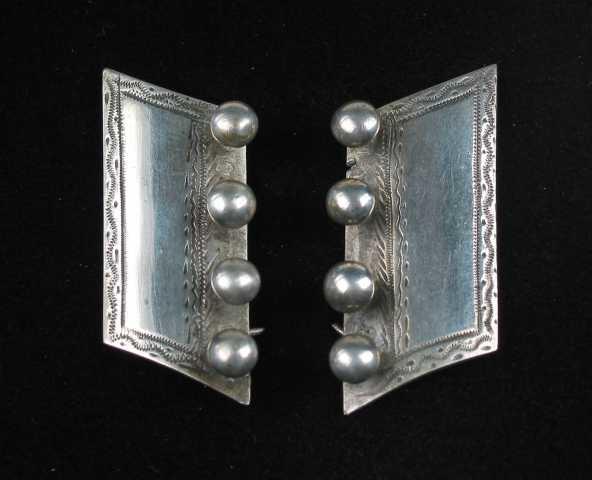 Hattespenne, snørespenne av sølv. Spennene består av av to like motsående deler. De er formet som et parallellogram med buet overflate. Oversida er dekorert med innpunslede rette og bølgete bånd. Langs kanten mot den andre halvdelen er det påsatt fire stifter med halvkuleformet hode. På baksida er det like under snorestiftene satt to spisse kroker til feste for beltet. Det holdes på plass ved å føres gjennom en påloddet hempe eller holder. På baksida er det to tårnformede stempler, trolig et bymerke