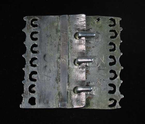 Støpt forgylt firkantet spenne i sølv med tre hektekroker. Spenna består av to deler, der den ene har tre kroker på undersiden, og den andre har tre tilsvarende hull utstanset i kanten. Hver av stykkene har et langsgående felt med støpte rosemønster. I hver rose er det en knupp- eller perlekruse omgitt av åtte små knupper. På hver langside ender platen i en gjennombrutt bord, eller en kam - Tudorkam, skilt fra det sentrale rosefeltet med to linjer. Spenna er slitt og har et gammelt preg. Hullstykket er forsterket med en plate på baksiden.