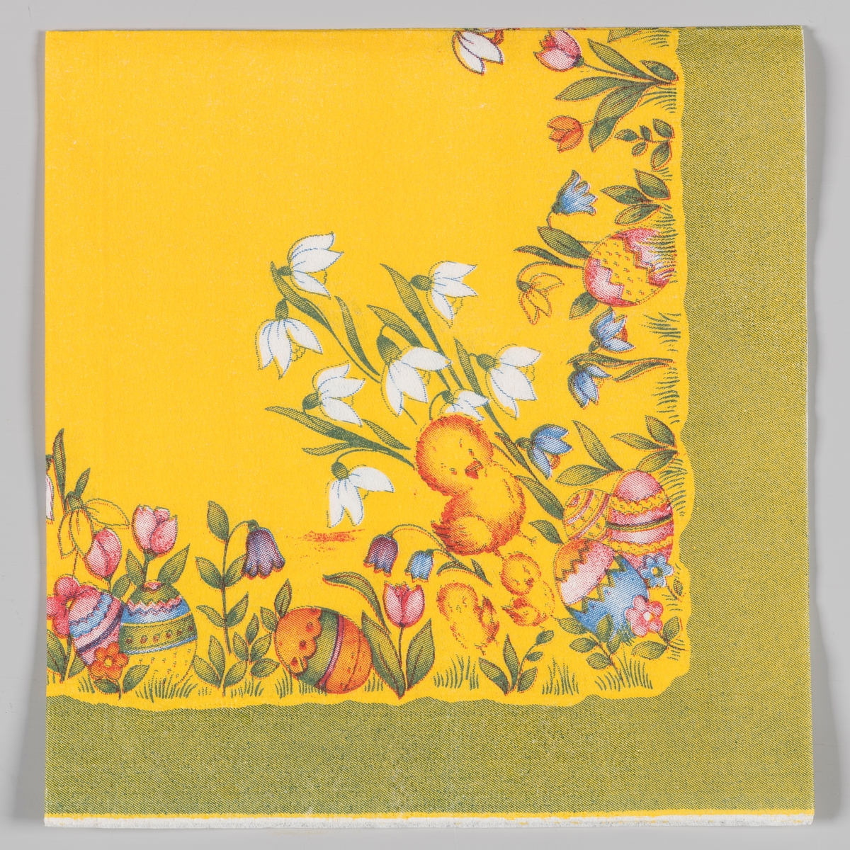 En stor kylling og to små kyllinger står blant kulørte påskeegg, snøklokker, skillaer og andre blomster