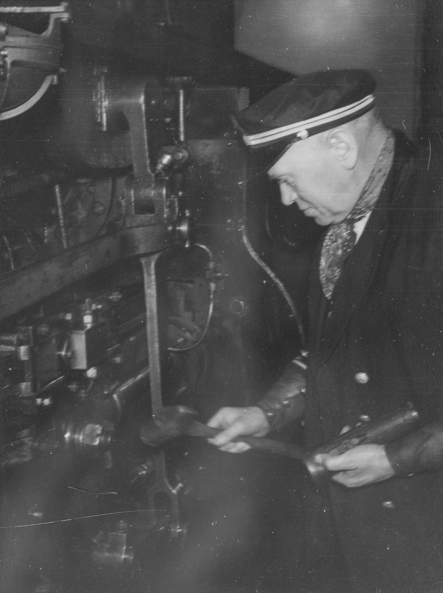 Lokomotivføreren smører maskinen på et damplok, trolig type 30.