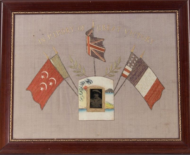 Brodert silkebilde med fotografi av ung mann. Midt i motivet fem ulike flagg som dekor rundt fotografiet. Fransk flagg, amerikansk flagg, Storbriannias flagg og trolig Ottomansk flagg (halvmåne og stjerner).