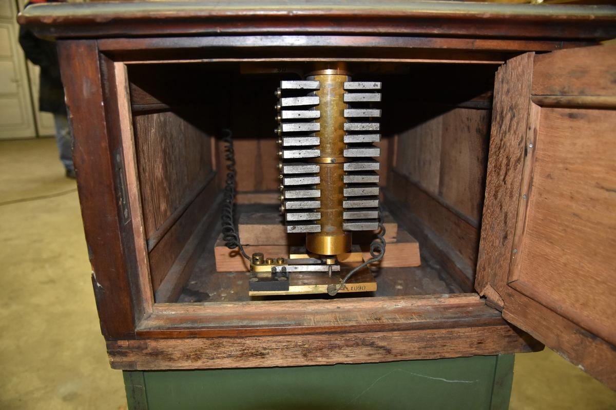 Morseapparat i rektangulær trekasse. På toppen har apparatet en rund bokstavskive med en hendel som kan flyttes til aktuell bokstav. bakenfor den runde skiven er det bygget opp et skap med skråstilt dør i fronten. Døren har fylling  med profillister og rundt glassvindu. Lås i nedkant. Gjennom vinduet kan ses to spoler, bak på skapryggen to hull med ledninger ut gjennom hullene. På toppen av skapet tilkoblingsskruer for ledninger. Under bokstavskiven, i front kan mekanismen i morsemaskinen sees gjennom  en dør som kan åpnes. Både døren og sidepanelene har fyllinger med profillister rundt