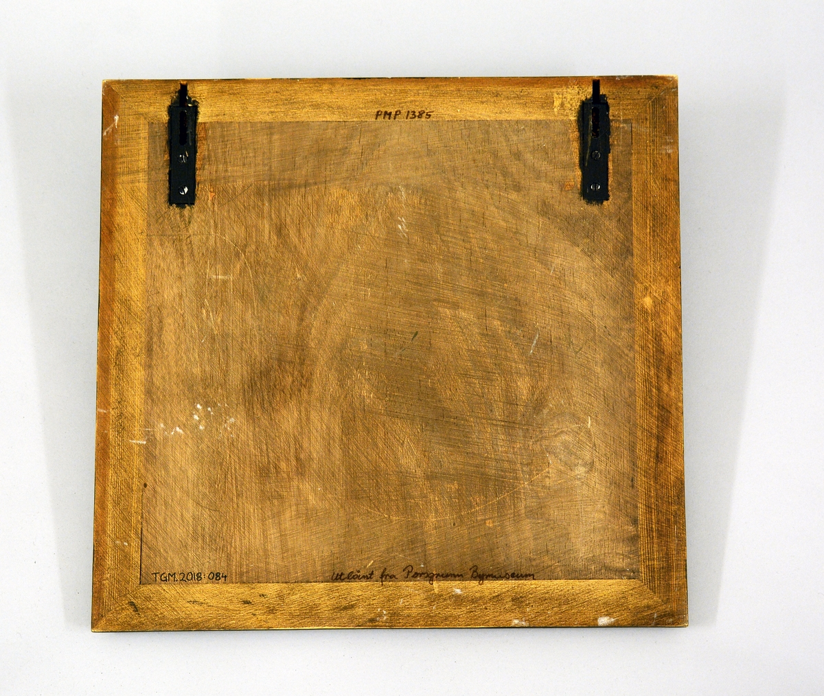 Relieff bestående av fire kvadratiske fliser med moskusmotiv montert på finérplate. I ytterkant av finerplaten er det montert en mørkebrun treramme. Kunstner: Konrad Galaaen.