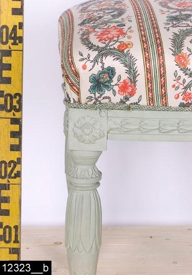 """Anmärkningar: Taburett, sengustaviansk, grönmålad, omkring 1800.  Stoppad sits med blomstertyg. Samtliga sarger har en lansettbladsbård av pastellage. I hörnen finns rosettanfanger i pastellage. Nedanför anfangerna finns överkragningar med skurna lansettblad och därunder skurna bladhölster med lansettblad (bild 12323__b). Nedåt avsmalnande ben med kannelyrer samt svarvade fotavslutningar. H:470 Br:445 Dj:425  Tillstånd: Stoppningen, tyget och färgen är senare. Undertill finns två senare förstärkningar.  Historik: Inköpt från domkyrkosyssloman Hugo Berggrens sterbhus, Västerås. Taburetten har deltagit i utställningen """"Samlat 1700-tal """". Taburetten har enligt kortkatalogen restaurerats 1985 (sannolikt ommålad i detta sammanhang). I kortkatalogen finns en bild på och en beskrivning av taburetten som gör gällande att den varit förgylld. Enligt kartkatalogen skall det också finnas ytterligare en taburett samt att invnr. skall vara 9924. En pall med invnr 12323  finns i 2003 års inventeringsförteckning över Vallby. Detta föremål registrerades av projektet Access på invnr. 9924 år 2007.  Negativnummer X-2759"""