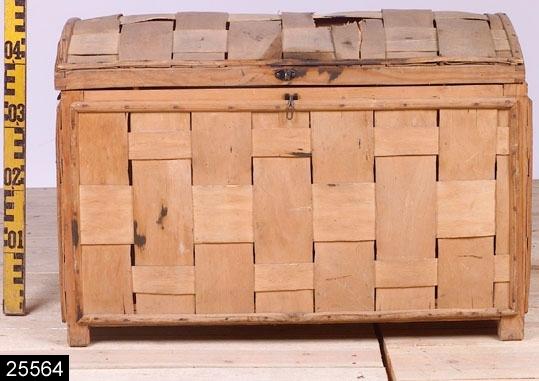 Anmärkningar: Kista, 1800/1900-tal.  Välvt gångjärnsförsett lock. Handtag av järn på sidorna. Hank och hankfäste av järn på framsidan. Kistan är uppbyggd på en stomme av furu och kring denna är spån av ljust lövträ flätat. H:480 Br:695 Dj:455  Tillstånd: Skador på ett flertal ställen. Några svarta fläckar (bläck?) framför allt vid låsbeslag och på fronten.