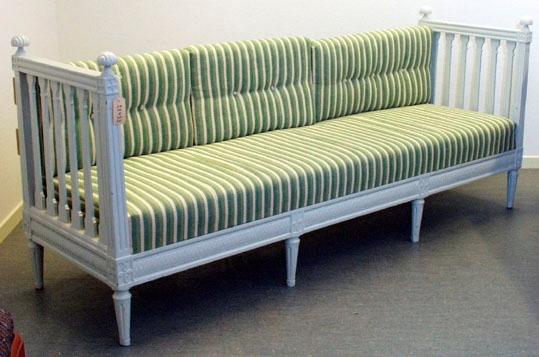"""Anmärkningar: Bankett, """"soffa"""" med falsk rygg av två plankor som spikats på vid senare tillfälle. Gustaviansk, gråmålad. Sidostycken: dekorerade på ovansida samt sidor med bandfläta. Pomponger vid ändarna. Rosettanfang, dekor med två knappar och kannelyrer på varje sida (de främre ståndarna har dekor på tre sidor och de bakre på två sidor). Sex kolonnliknande spjälor på vardera sidostycke. Sargen dekorerad med bandfläta och pärlstavar. Benen har rosettanfang, inslagen träplugg mitt i rosetten på anfangen på utsidan av sidostyckena. Framsidan har fyra rosettanfang. Fyra ben på framsidan, bara två ben i bakkant. Benen dekorerade med kannelyrer, vilka endast finns på benens framsidor eller sidorna (på sidostyckern). Bekbenen har 3 på sidorna, De främre sidobenen har 5 på fram och utsdor, de två benen mitt på framsidan har 3 kannelyrer."""