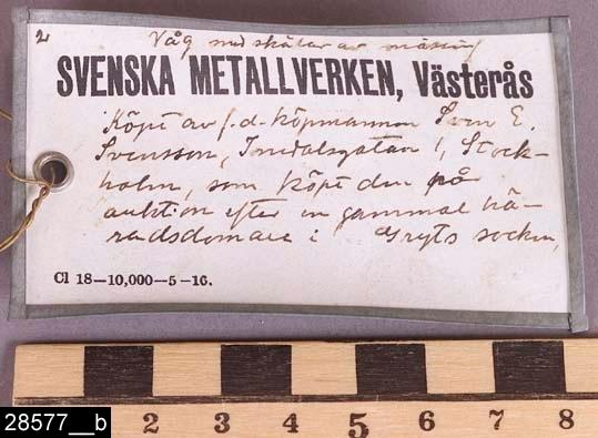 """Anmärkningar: Balansvåg, 1700/1800-tal.  Järnställning för upphängning. På ändarna finns rep och läderanordning som hänger från järnställningen. Längst ned på det högra repet sitter en vågskål av mässing. På järnställningen hänger en lapp där det står """"Våg med skålar av mässing SVENSKA METALLVERKEN, Västerås Köpt av f.d. köpmannen Sven E. Svensson, Tomtebogatan 1, Stockholm, som köpt den på auktion efter en gammal häradsdomare i Gryts socken."""" (bild 28577__b). H:410 L:310  Tillstånd: En vågskål saknas.  Historik: Gåva från SAPA AB, Division Service, 2002. Föremålet stod i ett skyddsrum på bruksområdet i Skultuna."""