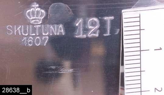 """Anmärkningar: Syltkittel, 1930/40-tal.  Rund nedåt avsmalnande kittel med två handtag. Till höger om det ena handtaget finns stämplar i form av en krona samt texten """"SKULTUNA 1607 12L"""" (bild 28638__b). Kitteln finns avbildad i kataloger från Skultuna under 1930-40-talen. I en katalog från 1945 framgår det att kitteln kostade 6,70 kronor och att den tillverkades i 7 storlekar (bild 28638__c). Jämför invnr. 28637-28639. Enligt en broschyr, utgiven av museet 2007 och benämnd """"Skultunastämplar 1800-2000"""", började den typ av stämpel som finns på föremålet användas 1922. Den användes fortfarande år 2007. H:190 D:355 Br:430 (avser måttet diameter samt handtagens mått)  Tillstånd: Nyskick.  Historik: Gåva från SAPA AB, Division Service, 2002. Föremålet stod i ett skyddsrum på bruksområdet i Skultuna."""