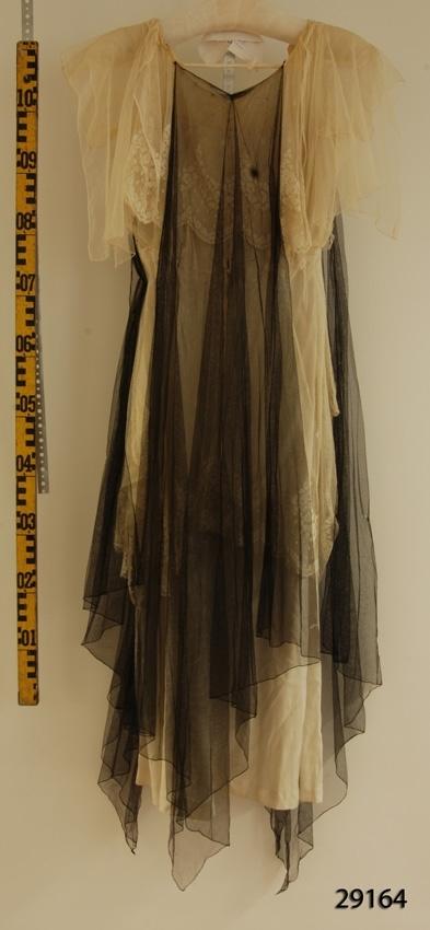 Anmärkningar: Irsta sn Gäddeholm Festklänning som använts av Elisabeth Beck-Friis gift Lewenhaupt. Född 1888 död 1982.  Lång klänning av ljusgult mjukt siden. Över livet ljusgul med blommor på grovmaskig tyll, liksom på kjolen från midjan och halvvägs ner, ärmar av samma sorts tyll i två lager, ett kort lager innerst och ett längre oregelbundet ytterst. Från halsringningen hänger ett löst svart släp av finmaskig tyll bak och två likadana fram. Har troligen en gång varit fästade med tryckknappar, numera fastsydda. Klänningen märkt med gul broderad isydd lapp med texten Stockholm A.B. Fr. V. Tunborgs Co. I ryggen ner till midjan knäpps klänningen med 14 hyskor på ena sidan som passas in i 14 ringar på andra sidan. Från midjan och neråt tre tryckknappar. Några hål finns i den svarta tyllen