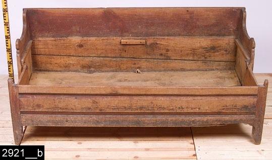 """Anmärkningar: Dragsoffa, omkring 1800.  Rakt bakstycke. Konturerade armstöd. Sits av trä som går att lyfta och underredet går att dra ut, då får man en säng som på bild 2921__b. Djupet blir då 815 mm. På sidorna finns järnkrokar och järnöglor som man kan fästa utdraget med. Framsidan av underredet är profilerat. H:730 L:1715 Dj:470  Dragsoffan är rödmålad och bär spår av naturligt slitage.  Tillstånd: Senare stöd baktill. Samtliga fötter är skadade. Hela dragsoffan är maskstungen. Skador vid flertalet kanter.  Historik: Inköpt från Gustafsson, N. Sylta, Munktorp sn vid Sven T. Kjellbergs besök. Enligt liggaren stod sängen i den """"gamla manbyggnaden"""".  Negativnummer X-266"""